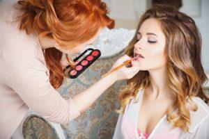 makeup artist applying makeup to a bride