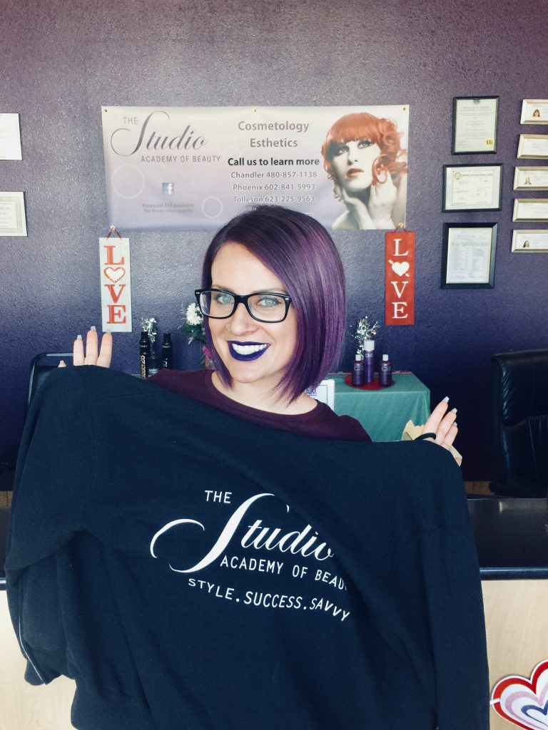 The Studio Academy of Beauty student holding school shirt