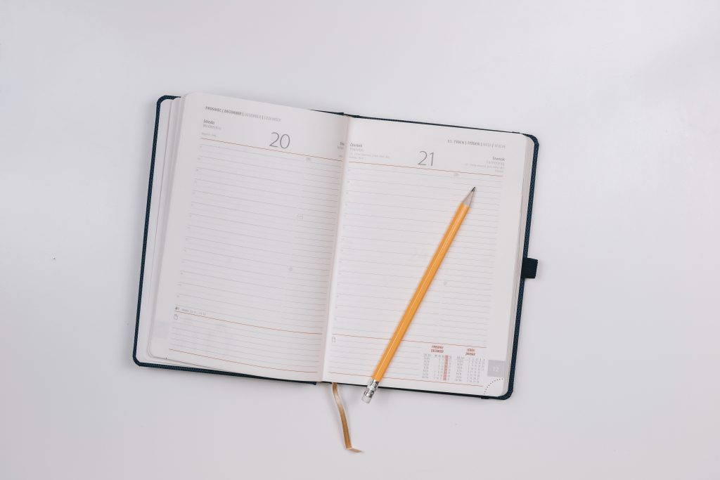 day planner and pencil on table